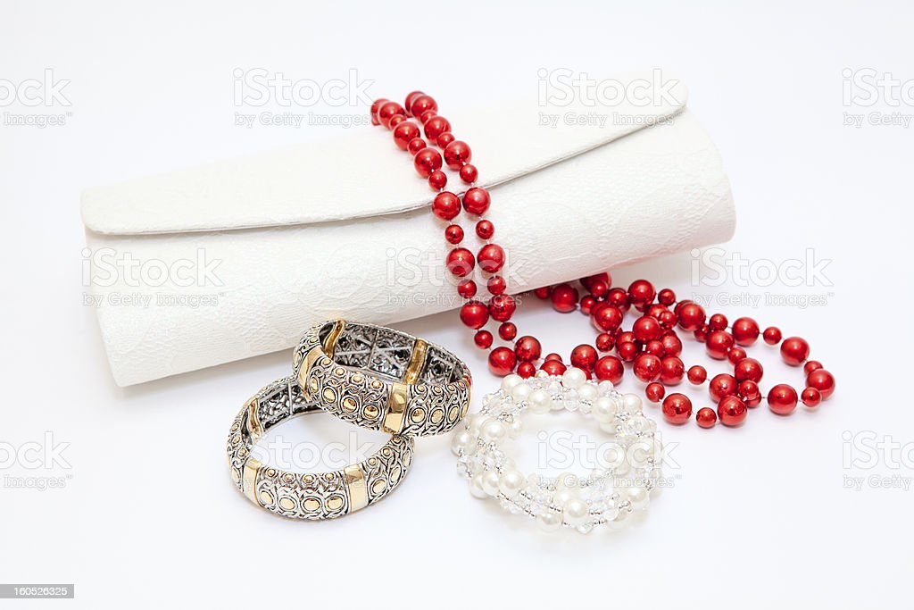Gold braceletes red and wite necklace with purse on white royalty-free stock photo