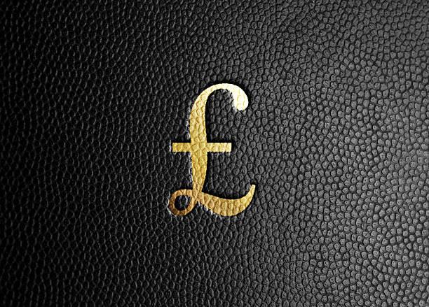gold british pound symbol on black leather - brokat stock-fotos und bilder