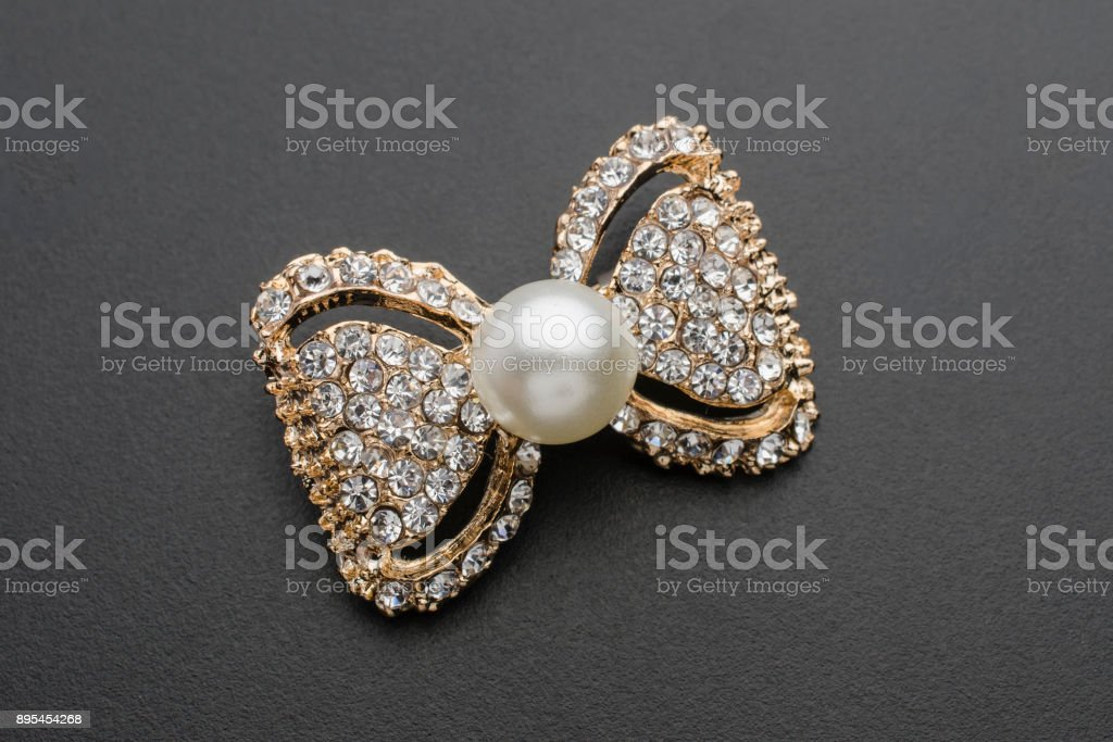 gold brooch bow with pearls and gems isolated on black stock photo