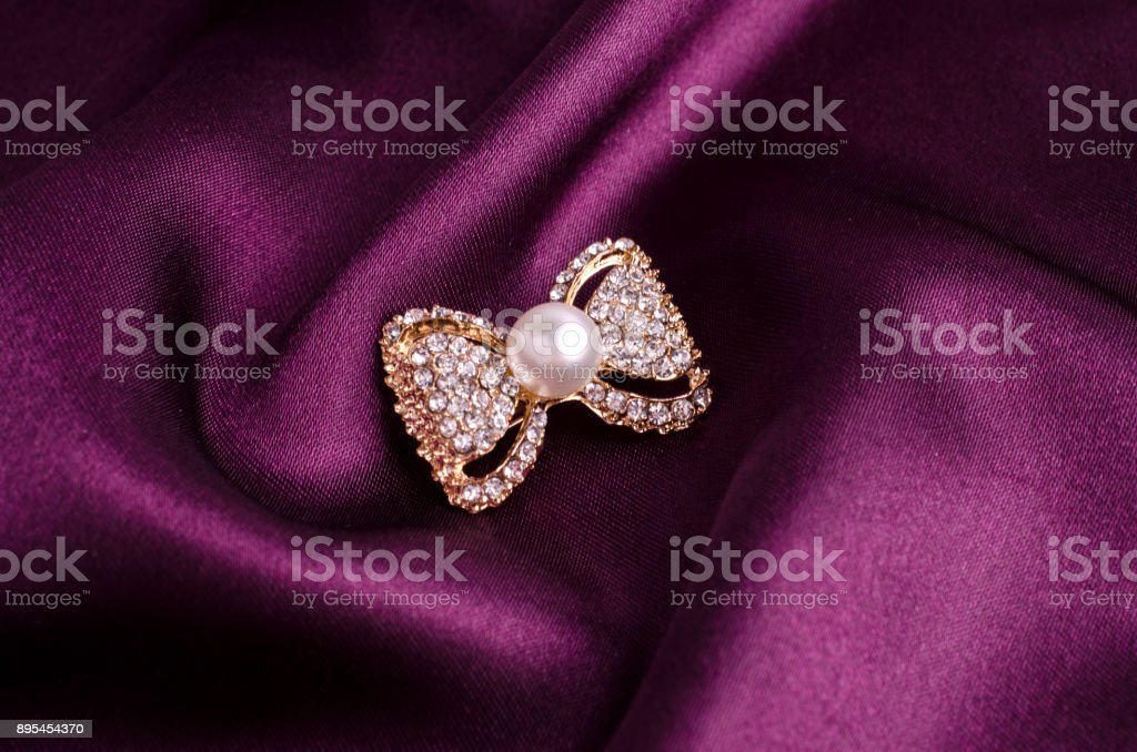 gold brooch bow with pearls and gems isolated on silk stock photo
