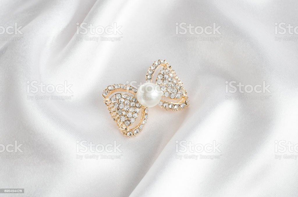 gold brooch bow with pearls and gems on silk stock photo