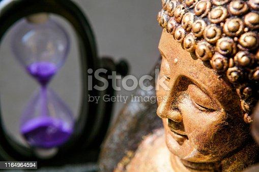 gold buddha face statue sand clock