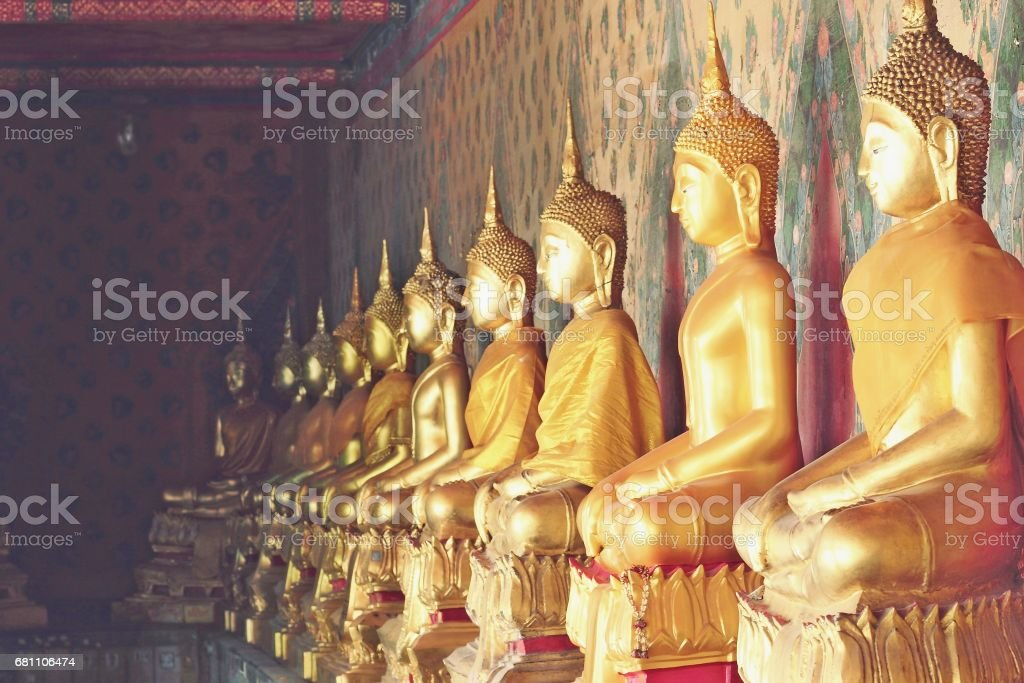 Gold Buddha statues and clothed in yellow robe stock photo