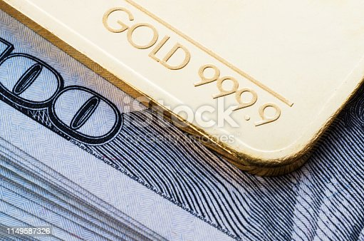 Gold bullion 999.9 fineness against the background of a hundred-dollar bills.