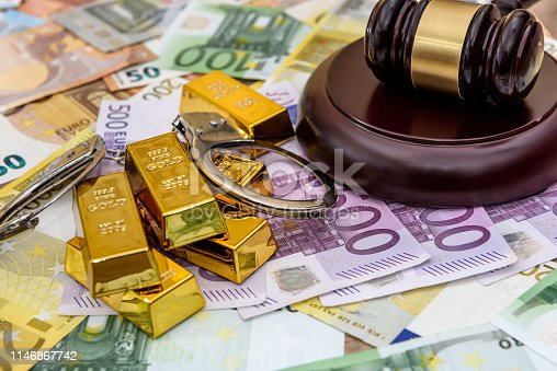 istock Gold bullions with judge's gavel and handcuffs on euro banknotes 1146867742