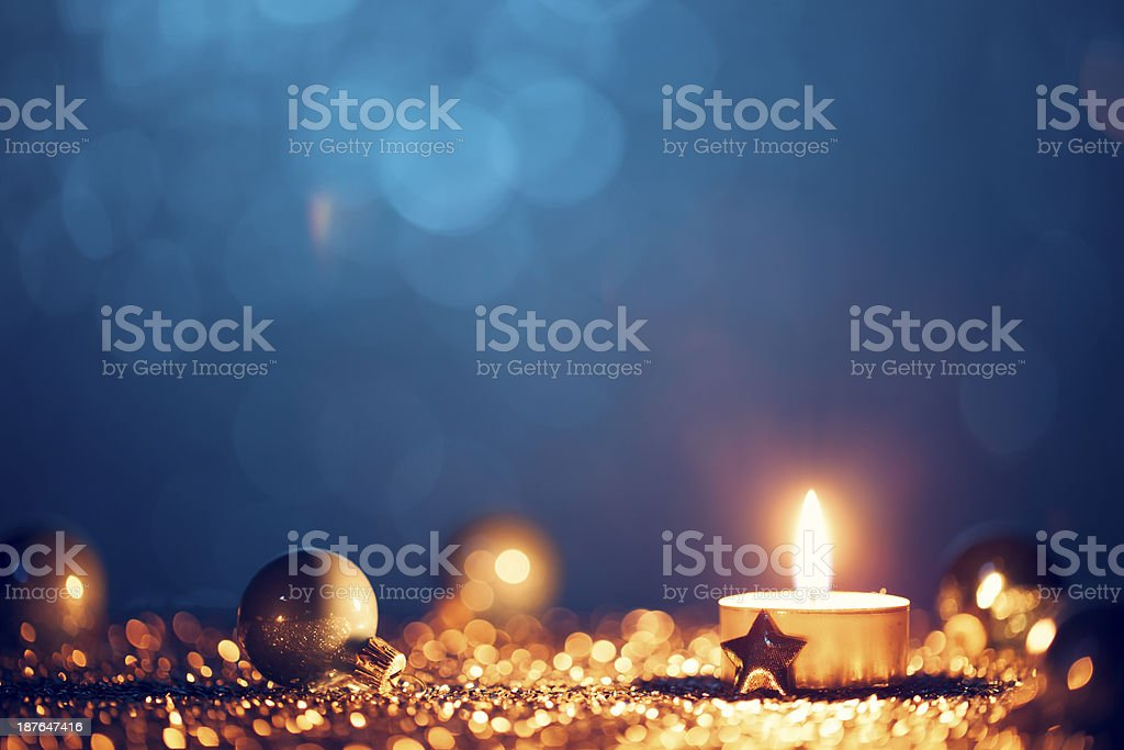 Gold candle and ornaments with blue background royalty-free stock photo