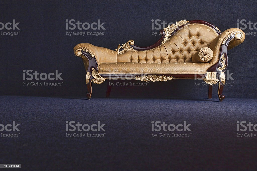 Gold Chaise Longue In A Dark Room stock photo