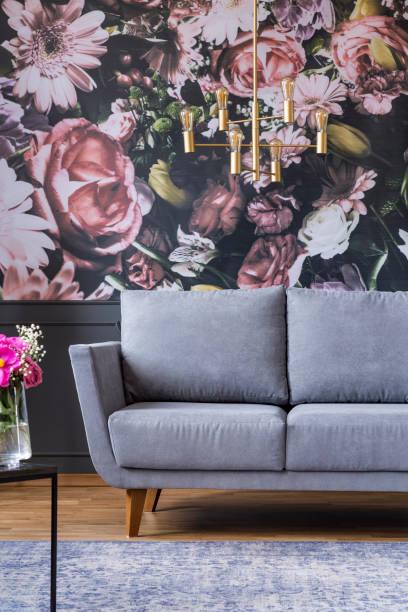gold kronleuchter oben grau sofa im wohnzimmer interieur mit blumen-print an der wand. echtes foto - blumendrucktapete stock-fotos und bilder