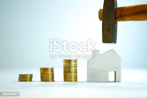 istock Gold coin stacked 3 step or graphs with wooden home on a white background, Money to repair or build a new home concept 932606022
