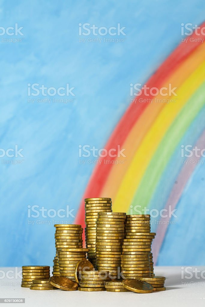 Gold coins against blue sky and rainbow background stock photo