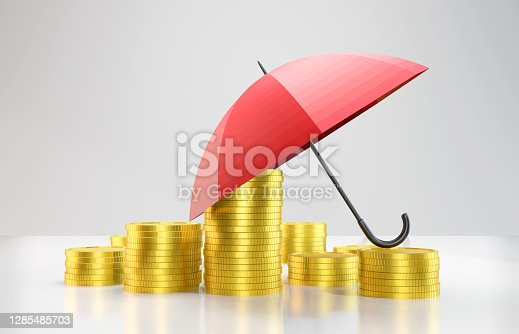 Gold coins and umbrella stacked on top of each other. insurance concept. Horizontal composition with copy space.