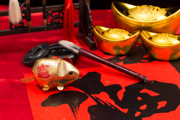 gold coins, gold ingot, calligraphy brushes, couplets and mascots for the year of the rat - chinese new year stock pictures, royalty-free photos & images