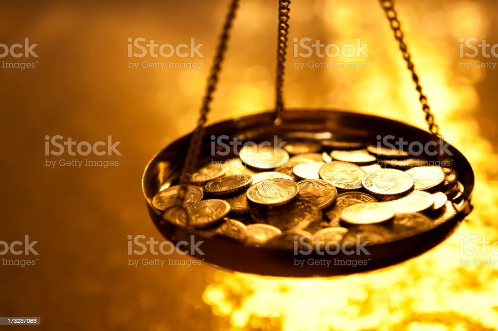 Gold coins on a weight scale royalty-free stock photo