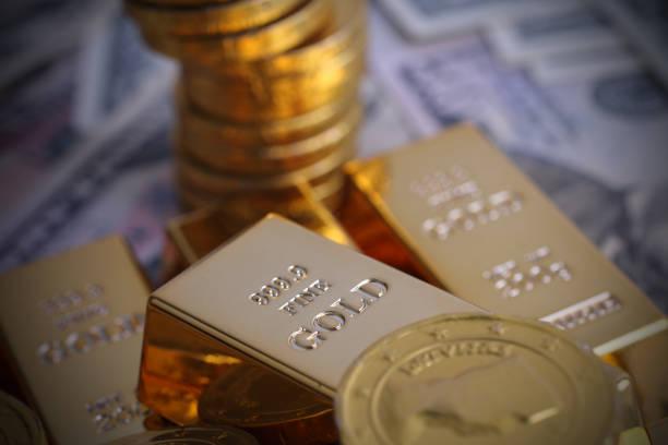 Moedas de ouro com um lingote de ouro - foto de acervo