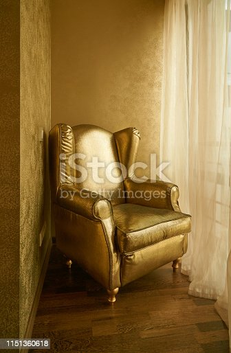 Gold color textile armchair and interior in apartment loggia