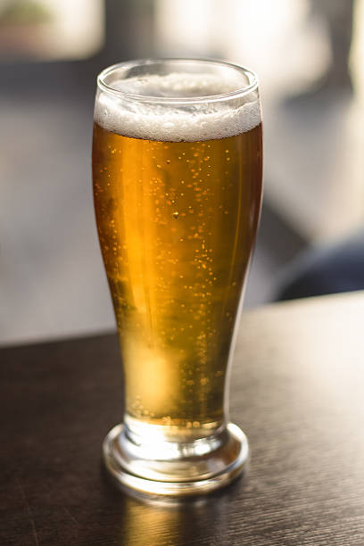 Gold color frosty beer A big glass of gold color frosty beer. pilsner stock pictures, royalty-free photos & images