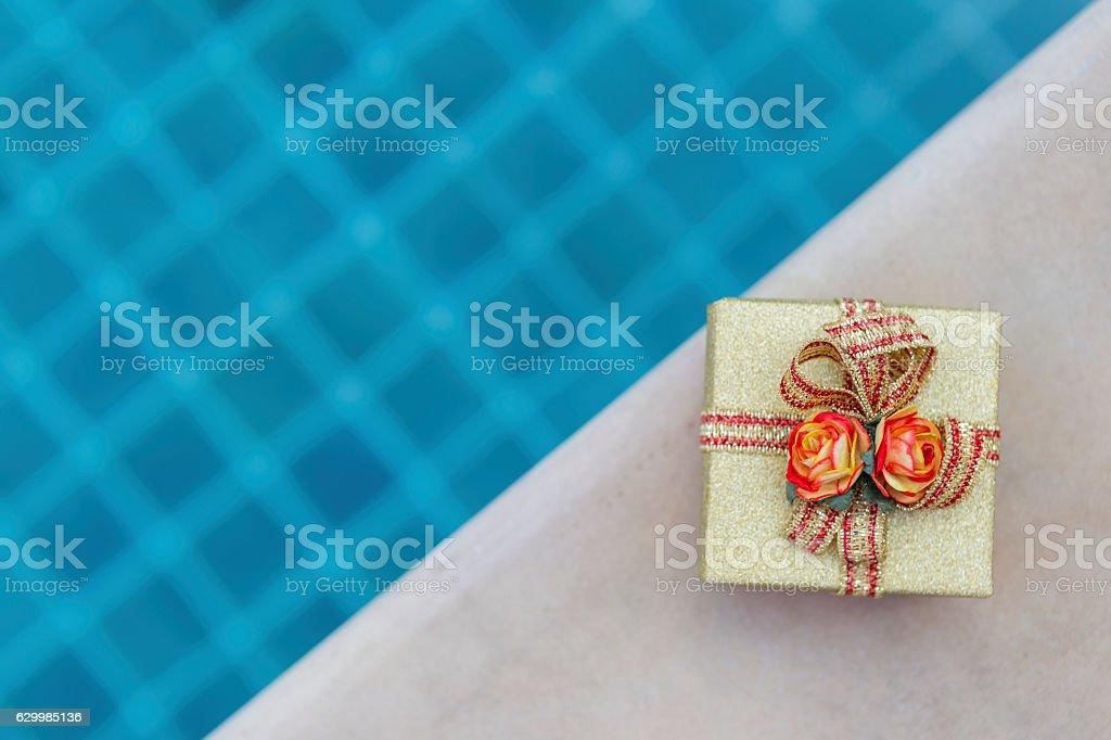 Gold color gift box on swimming pool edge - foto de acervo