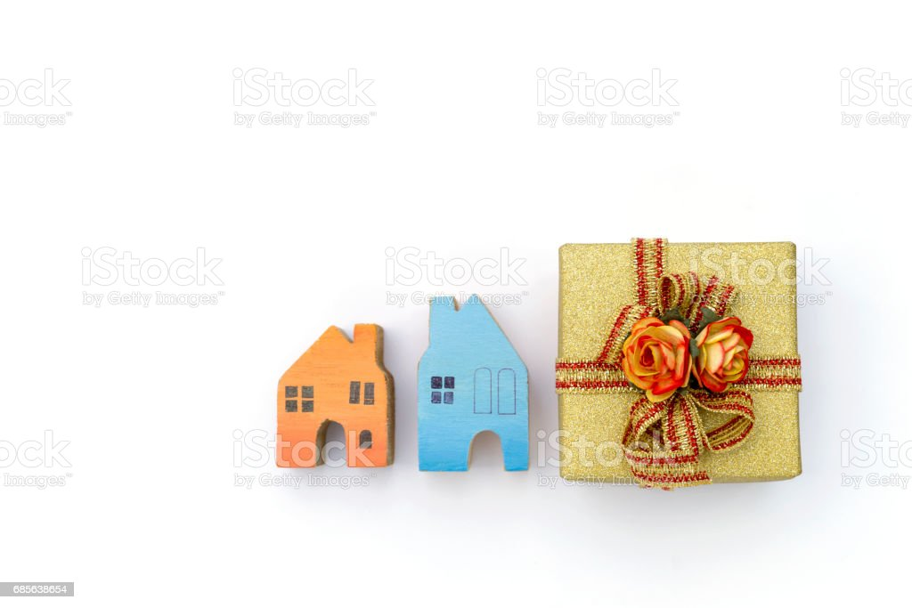 Gold color gift box with wooden miniature house on white background royalty-free 스톡 사진