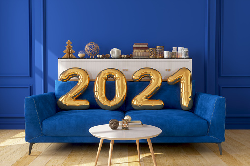 Gold Colored 2021 Year Balloons On The Sofa With Blue Wall.