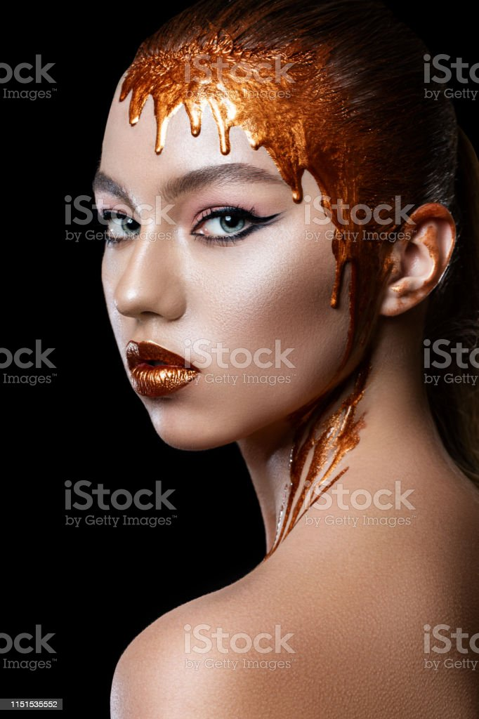 Gold colors flow down from the lips, face and neck of a beautiful...