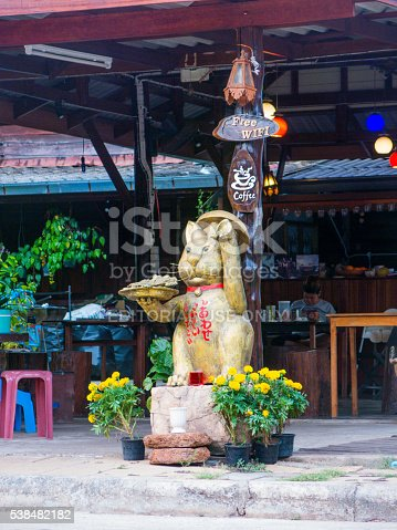 istock Gold Coloured Cat Statue and Incidental Man Sitting 538482182