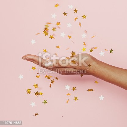 Gold confetti stars decoration in female hand on pastel pink background