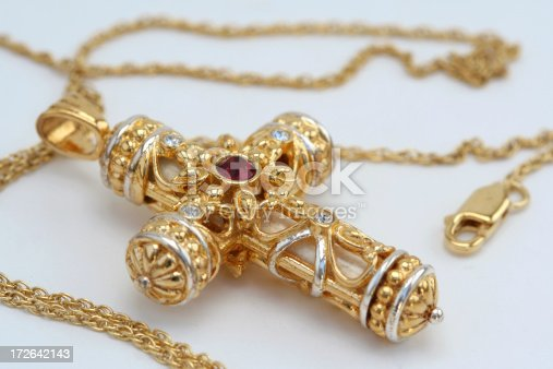 This is a gold cross necklace with an  amethyst jewel in the middle of it.
