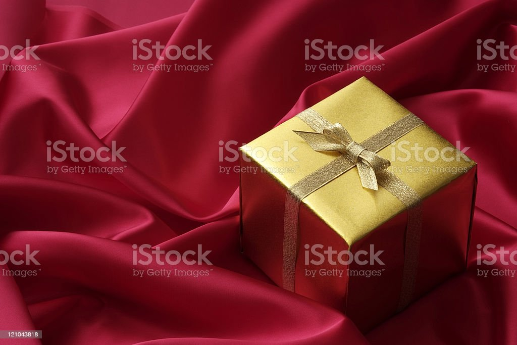 High angle view of gold cube gift box with gold ribbon on red satin...