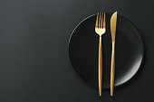 Beautiful gold cutlery - fork and knife on black plate on black background. Top View, above. Horizontal.