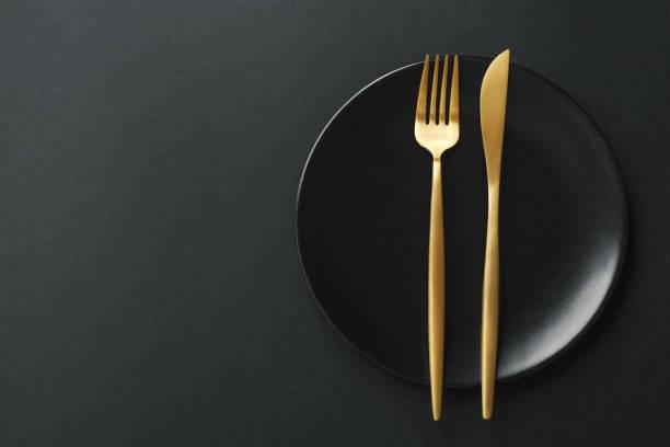 gold-besteck auf schwarzem hintergrund - tafelbesteck stock-fotos und bilder