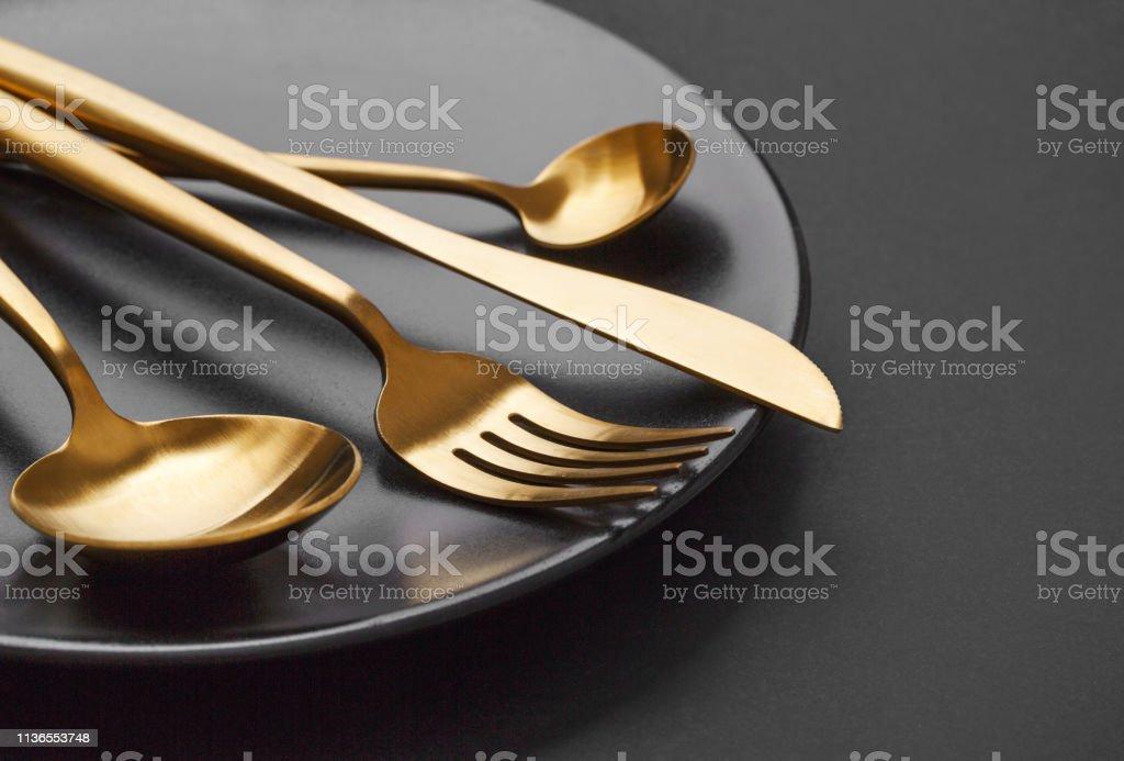 Gold cutlery set on black background - Zbiór zdjęć royalty-free (Bez ludzi)