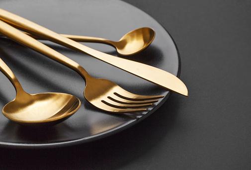 Gold Cutlery Set On Black Background - zdjęcia stockowe i więcej obrazów Bez ludzi