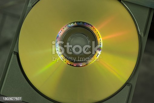 istock Gold DVD compact disc on the open tray of the player 1302627527
