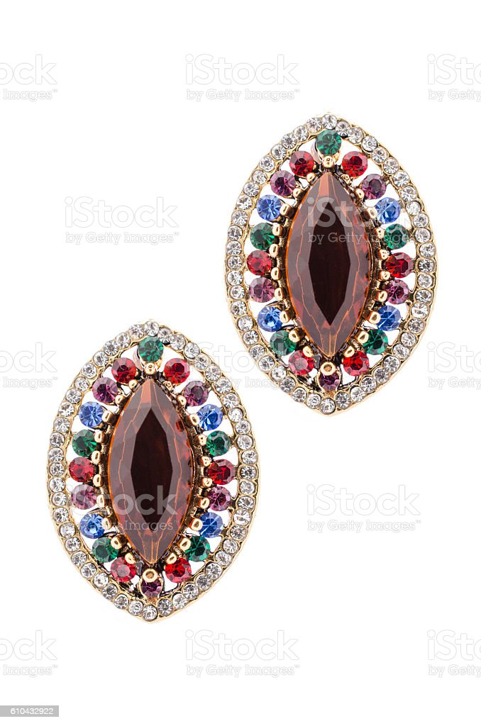 Gold earrings inlaid with  gemstones on a white background stock photo