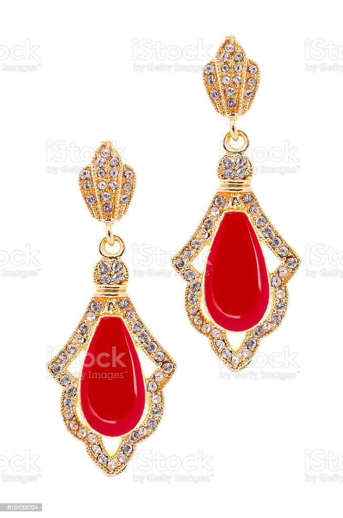 Gold earrings with red stone on a white background stock photo