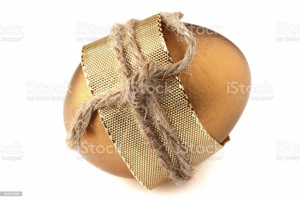 Goldene Osterei umwickelt mit goldenen Schleife und Seil Lizenzfreies stock-foto