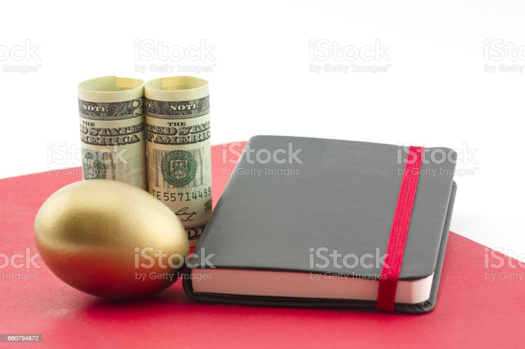 Gold egg, dollars, red folder and journal reflect planned success stock photo