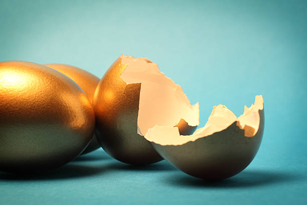 Gold Eggs and Shell Gold eggs and cracked open shells. nest egg stock pictures, royalty-free photos & images