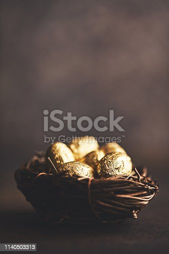 Gold eggs in nest. Easter background