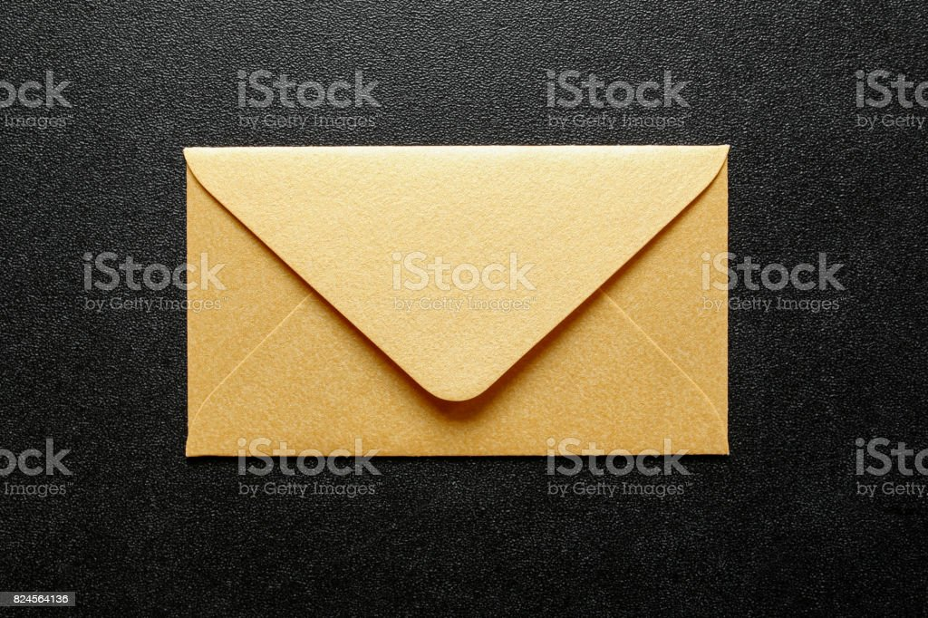 gold envelope on black background stock photo