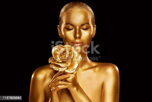 Gold Fashion Model Beauty Portrait with Rose Flower, Golden Woman Art Luxury Makeup on studio black background, Studio shot over black background