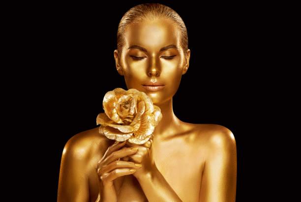 Gold Fashion Model Beauty Portrait with Rose Flower, Golden Woman Art Luxury Makeup on studio black background stock photo