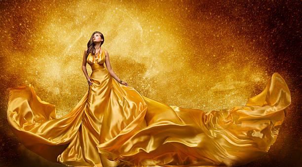 gold model kleid, frau golden abendkleid aus seide fließendes material - lange abendkleider stock-fotos und bilder