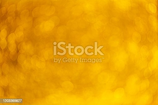 621116812 istock photo Gold Festive Christmas background. Elegant abstract background with bokeh defocused lights and stars 1203365627