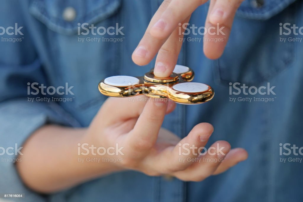 Gold fidget spinner in hand. Popular trendy toy close-up. stock photo