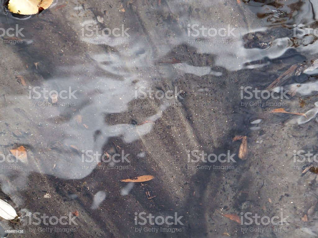 Gold flakes in water stream stock photo