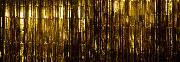 壁のスタジオにぶら下がっているゴールドフォイルストリップカーテン - glitter curtain ストックフォトと画像