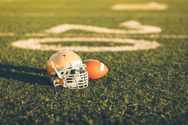 Gold Football Helmet on Field stock photo