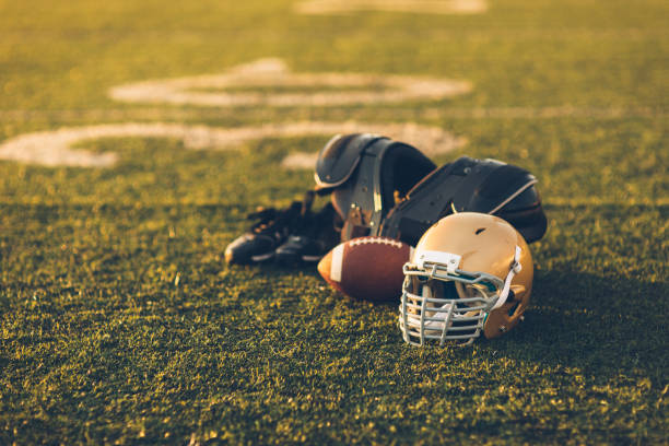 Gold Football Helmet on Field A Gold American Football helmet sits with a football on a football playing field. The light is from the sun which is about to set, shallow depth of field. Copy space included. Sport background image. american football uniform stock pictures, royalty-free photos & images