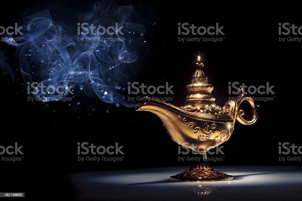 A gold genie lamp with smoke on black background stock photo